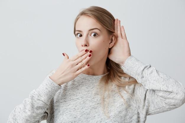Giovane femmina bionda attraente stupita sorpresa che ha stupito espressione del fronte, coprendo bocca aperta di mano