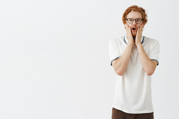 Ragazzo rosso barbuto sorpreso e stupito in posa contro il muro bianco con gli occhiali