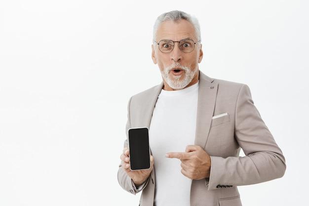 Uomo d'affari sorpreso e stupito in tuta puntare il dito sullo schermo dello smartphone, mostrando l'applicazione
