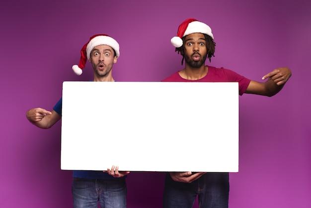 Удивленные. изумленные друзья в новогодней шапке держат белый баннер для вашего сообщения.