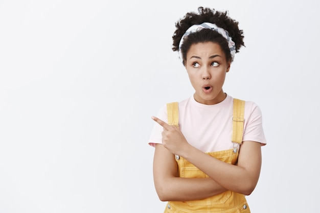 Surprised and amazed good-looking teenage girl with dark skin and curly hair in headband and yellow overalls, eavesdropping about classmat, pointing at upper left corner, standing with folded lips