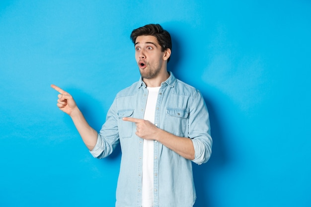 Surprised and amazed man looking at promotion, pointing fingers left at advertisement, standing over blue background.