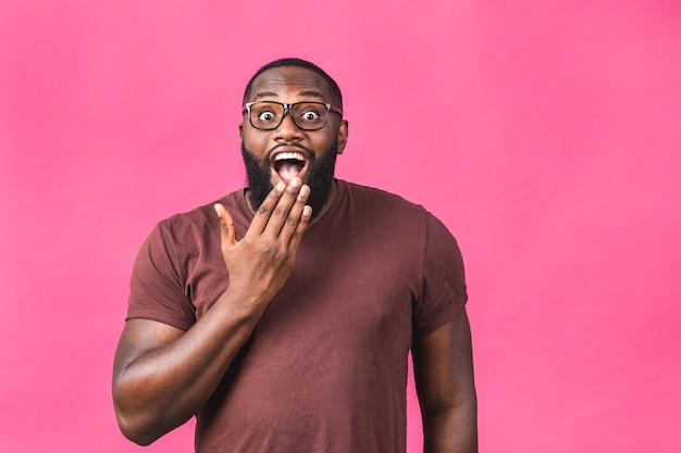 분홍색 배경 스튜디오 초상화 위에 캐주얼하게 고립된 아프리카계 미국인 남자가 깜짝 놀랐습니다. 사람들이 라이프 스타일 개념입니다. 복사 공간을 비웃습니다. 입을 벌리고 있습니다.