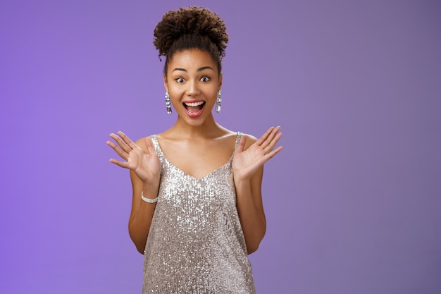 Surprised amused excited african-american woman in glittering shiny silver dress raise hands astonished pleased delighted meeting friend party smiling thrilled standing blue background amazed.