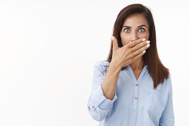 驚いた面白がって中年の女性ブルネットは正面を凝視し、口を無言で覆い、手のひらの唇を驚かせ、うわさ話をし、驚くべき噂を聞き、白い壁をポーズします