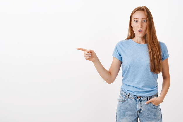 青いtシャツのそばかすのある驚きのびっくりした魅力的な生姜の少女は、目を飛び出し、唇を飛び出して目を飛び出し、印象的なポインティングポインティングを見つめる
