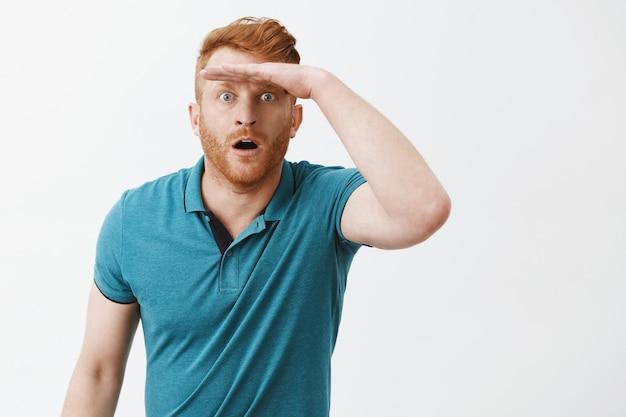 Удивленный и изумленный европеец в зеленой футболке держит ладонь на лбу и задыхается с открытым ртом, глядя вдаль и вдалеке видит что-то впечатляющее