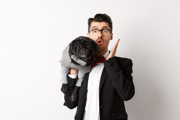 Удивленный и изумленный владелец собаки в костюме, глядя в камеру, держит на плече симпатичного черного мопса, животное в костюме, позирует на белом.