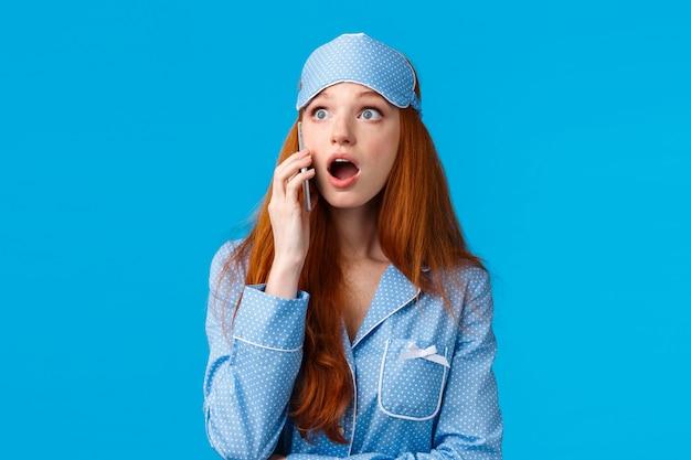 驚いて、驚いて、赤毛の女の子が電話で話している感動をあえぎながら驚かせた