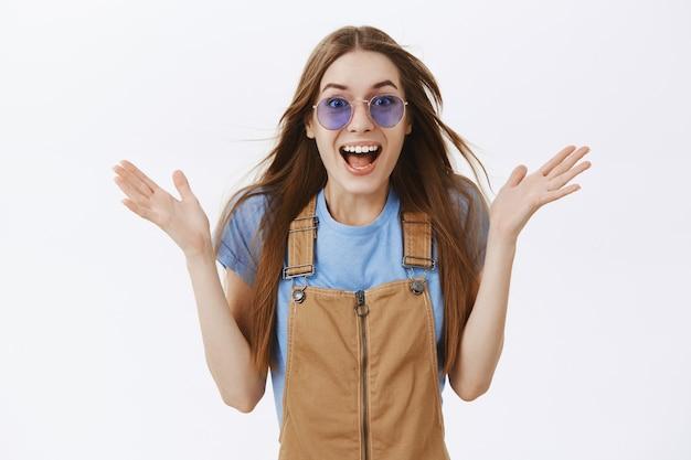 Удивленная и удивленная привлекательная девушка, поднимающая руки в сторону, счастливая, возбужденная, в солнечных очках