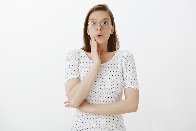 Удивленная и удивленная женщина в очках с волнением слушает