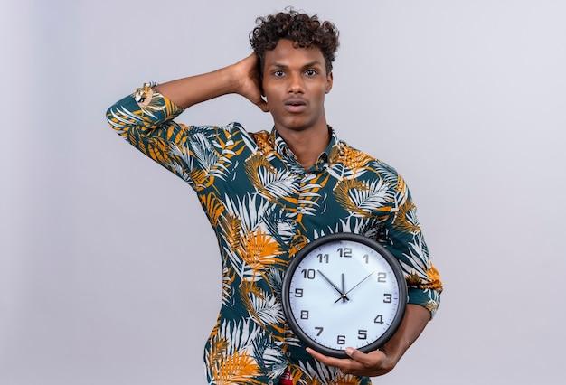 Удивленный и сбитый с толку молодой красивый темнокожий мужчина с вьющимися волосами держит руку на голове и держит настенные часы на белом фоне