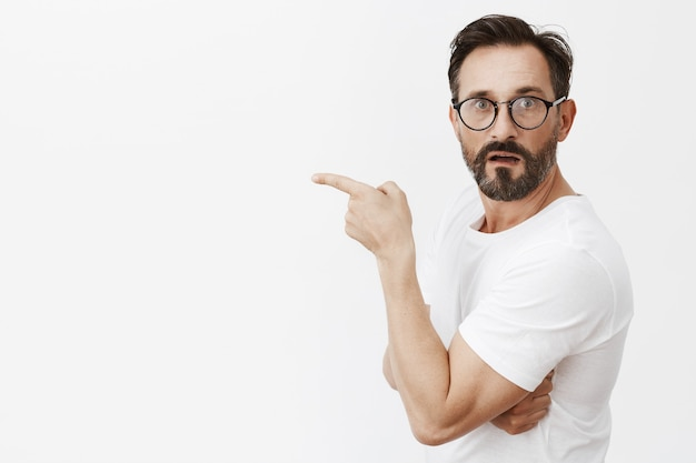 眼鏡をかけてポーズをとって驚いて好奇心旺盛なひげを生やした成熟した男