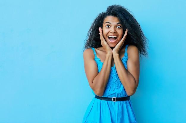 青いサマードレスを着た驚いて興奮しているアフリカの女性は、目と口を大きく開いてポーズをとり、手のひらに顎の音を聞き、カメラを見ています。