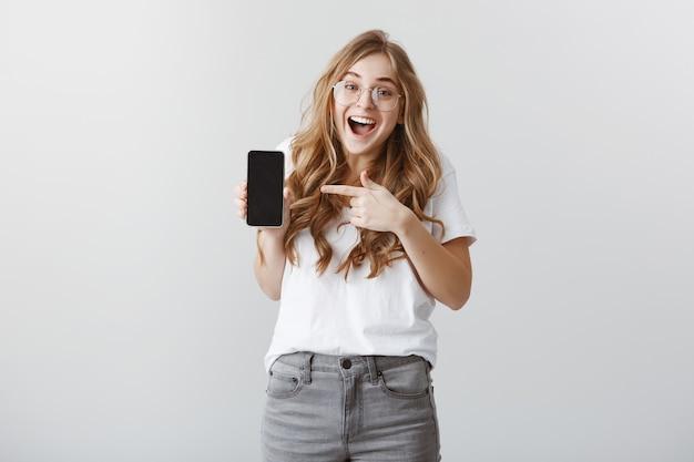 Удивленная и возбужденная блондинка в очках, указывая пальцем на дисплей мобильного телефона, показывая приложение