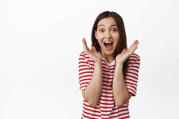놀라고 흥분한 갈색 머리 여성, 행복에서 비명을 지르고, 승리하고, 승리하고 축하하며, 흰 벽에 티셔츠를 입고 서 있습니다.