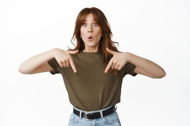 驚いて興奮している女の子が指を下に向けて、白の上に立って驚いたと言います