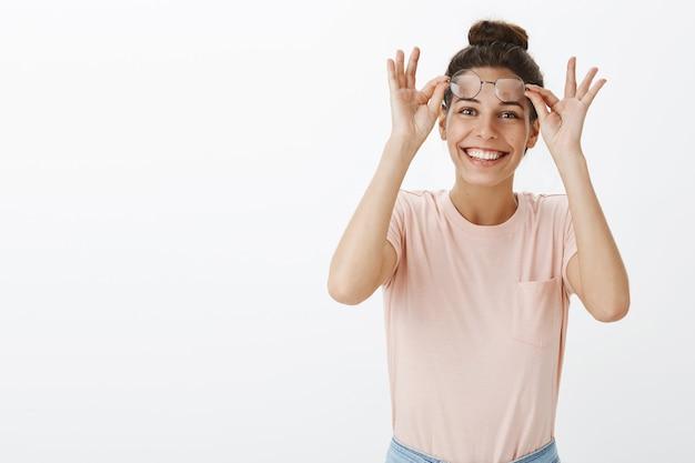 白い壁にポーズをとって眼鏡をかけて驚いて興奮した女の子