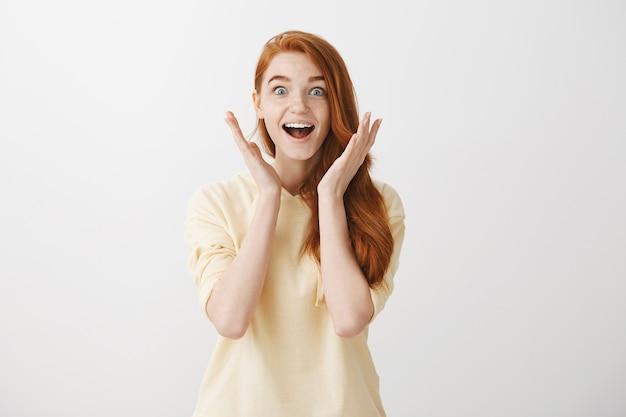 驚きと興奮のかわいい赤毛の女の子は素晴らしいニュースに反応します
