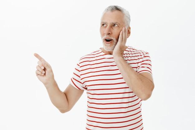 Удивленный и взволнованный старший мужчина реагирует на потрясающее промо, указывая и глядя в левый верхний угол