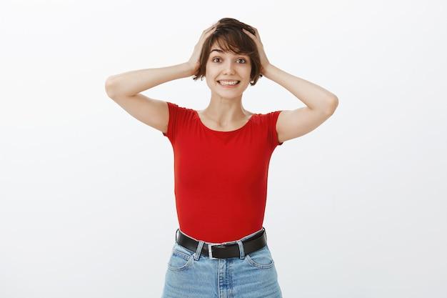Удивленная и возбужденная женщина в изумлении хватается за голову и весело улыбается