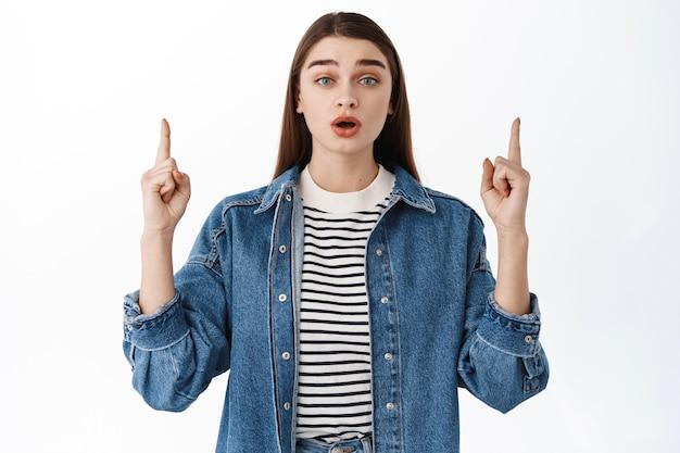 新製品について話し、発表し、そこを見て、指を上に向けて驚いて見、広告を表示し、白い壁の上に立っている、驚いて興奮している女性