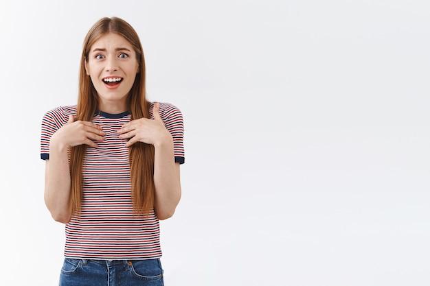 Удивленная и польщенная симпатичная молодая европейка в полосатой футболке, прижатая ладонями к груди и вздыхая от веселья и сочувствия, радостно улыбается, получает потрясающий подарок, стоит на белом фоне