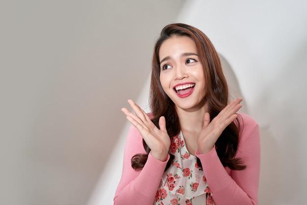 スタジオの白い背景の上に興奮して分離された見て驚いて幸せな若い感情的な女性