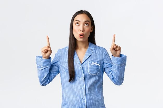 Удивленная и впечатленная азиатская девушка в синих джемми смотрит и показывает пальцами на промо-баннер. женщина в пижаме отвисла при виде классного рекламного объявления