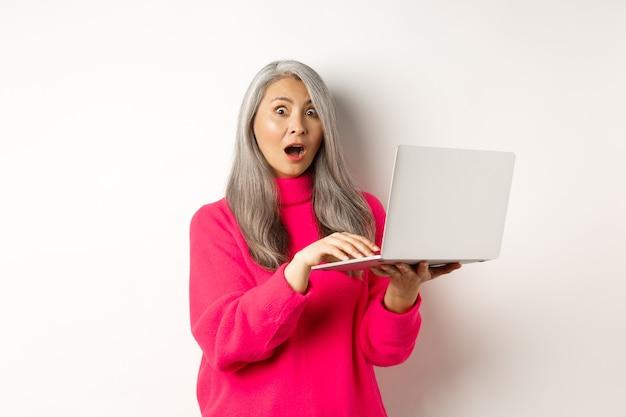 Удивленная и впечатленная азиатская бабушка потрясенно уставилась в камеру после прочтения новостей на ноутбуке ...