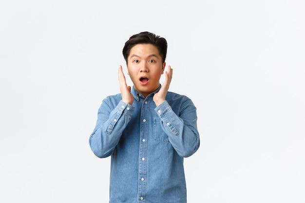 놀라움과 감동을 받은 아시아 남자는 큰 발표에 반응하여 얼굴 가까이 손을 잡고 숨을 헐떡이며 믿을 수 없는 것을 응시하고 흰색 배경 위에 놀란 채 서 있습니다.