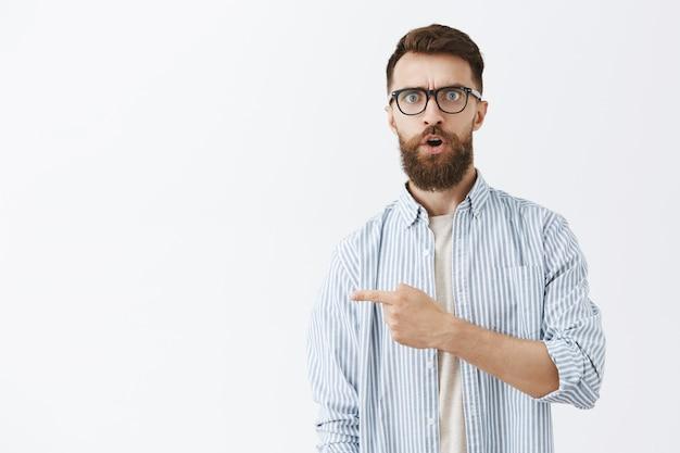 Удивленный и впечатленный бородатый мужчина позирует у белой стены