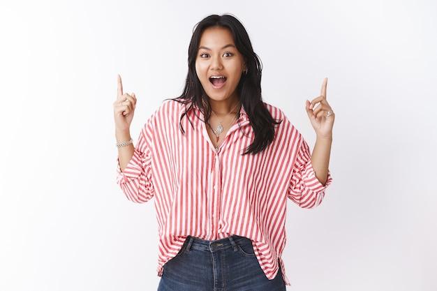 줄무늬 블라우스를 입은 귀여운 말레이시아 여성은 좋아하는 가게에서 놀라운 할인을 받고 손을 들고 흰 벽 너머로 흥분되고 즐거운 느낌을 가리키며 놀라고 감동을 받았습니다.
