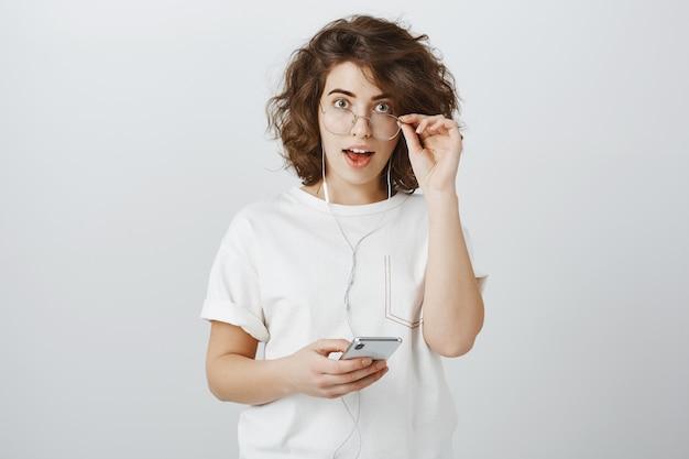 Удивленная и заинтересованная молодая женщина выглядит взволнованной, используя наушники и мобильный телефон