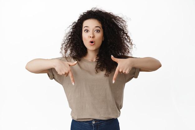 驚いて興味をそそられた女性ショップの顧客が指を下に向けて、素晴らしい価格のセールを見せ、驚いて、すごいと言って、白のロゴを示します