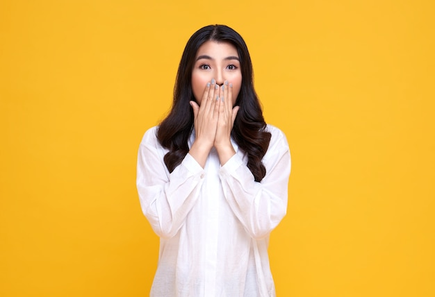 明るい黄色で隔離された手で口をコーニングする驚きとショックを受けたアジアの女性。