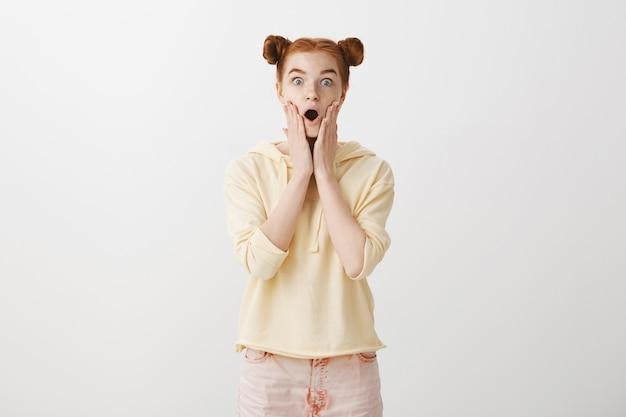 Удивленная и шокированная рыжая девушка выглядит изумленной