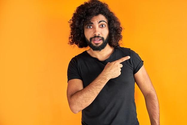 Удивленный арабский парень в черной повседневной футболке, указывая пальцем в сторону