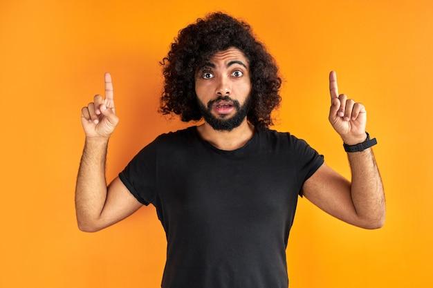 Удивленный арабский парень в черной повседневной футболке, указывая пальцем на вверх