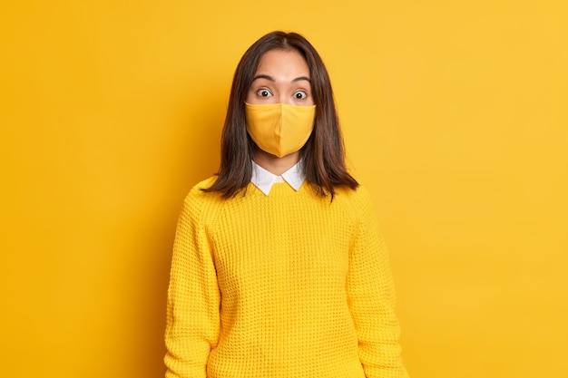Surprised asia woman in protective disposable mask prevents catching contagious disease