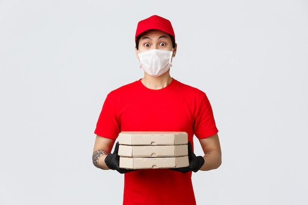 Surprised asian delivery guy look embarrassed as someone opened door naked, holding pizza as clients made order from food deliver app. courier in red cap and t-shirt uniform, medical mask and gloves