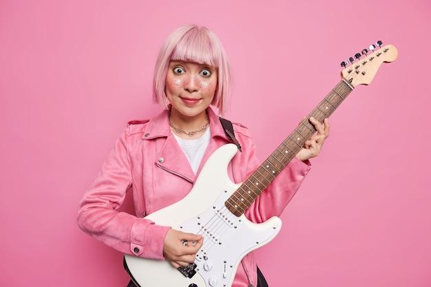 핑크색 머리를 가진 깜짝 아시아 여성 가수가 일렉트릭 기타를 연주하는 인기 밴드 재능있는 뮤지션이 스튜디오에서 록 음악을 연주하며 콘서트를 준비합니다. 레트로 스타일. 악기
