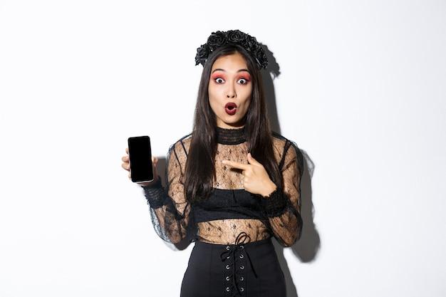 Удивленная азиатская девушка в черном готическом платье с венком, задыхаясь от удовольствия и указывая пальцем на дисплей мобильного телефона, показывая баннер или промо хэллоуина, стоя на белом фоне.