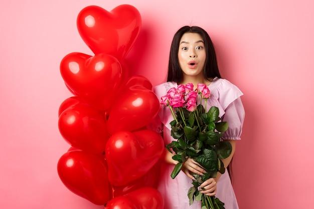Удивленная азиатская девушка в платье, стоящая рядом с воздушными шарами в виде сердца на день святого валентина, и говорит вау в камеру, держа в руках букет цветов от любовника, романтическое свидание с розами, розовый фон.