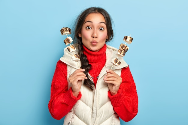 Удивленная азиатская девушка держит губы округлыми, держит палочки с жареным зефиром над костром, наслаждается пикником с друзьями, носит теплый красный свитер и жилет, позирует у синей стены