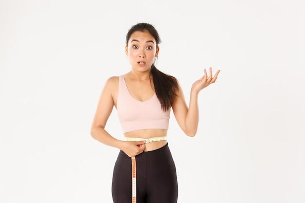 ダイエット中の驚いたアジアの女の子、スポーツウーマンはウエストに巻尺を巻いて、トレーニングで体重が減ったように見えます。