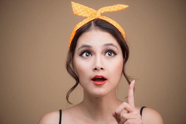 Удивленная азиатская девушка с красивой улыбкой в стиле кинозвезды на желтом фоне