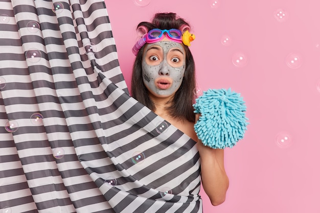Surprised asian woman applies facial clay mask takes shower holds sponge prepares for date has perfect body feels relaxation and relief isolated over pink background with soap bubbles.