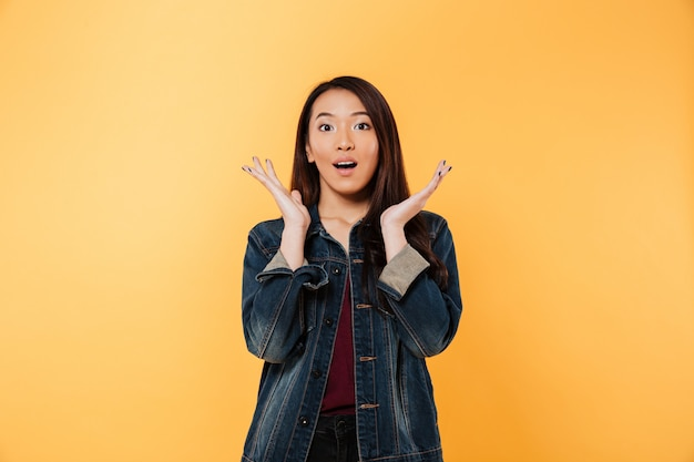 Surprised asian woman in denim jacket holding arms near face and looking at the camera over yellow background