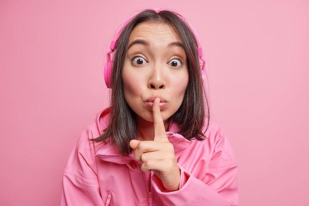 신비한 표정으로 놀란 아시아 여성이 조용히 말하면 금기 제스처가 무선 헤드폰을 통해 음악을 듣고 분홍색 벽에 고립 된 재킷을 입습니다. 조용히하세요.